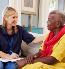 caregiver helping the senior woman with a smile