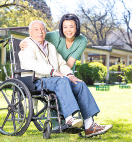 caregiver and senior man in the wheelchair are smiling