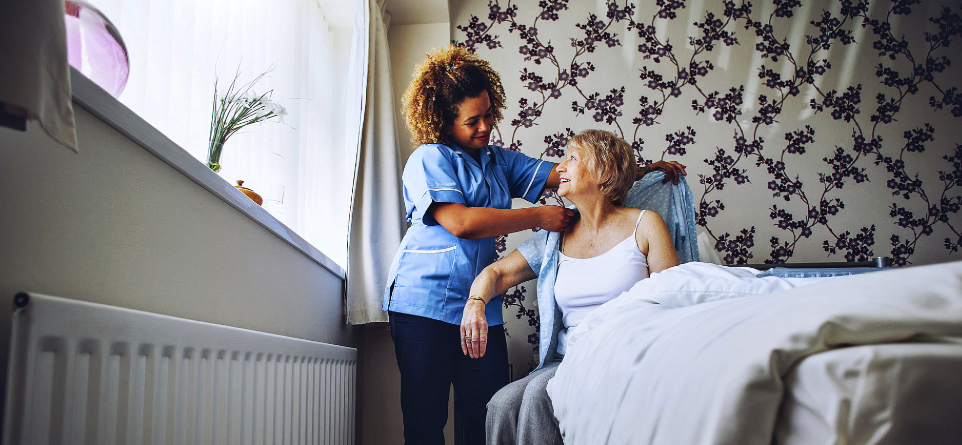 caregiver is helping to wear the clothes of the senior woman